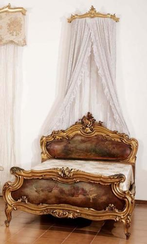 A gilt and painted wood bed