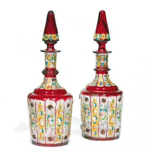 A pair of enamelled ruby and clear glass bottles and stoppers