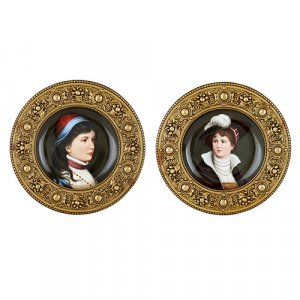 Two Austrian circular painted porcelain plaques in brass frames