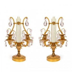 A pair of lyre shaped ormolu and crystal two light table candelabra