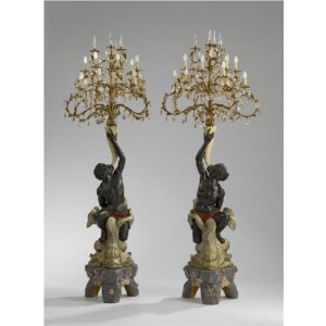 A pair of large Blackamoore figures holding twelve light candelabra