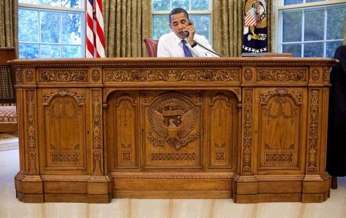 Photo of President Barack Obama seated at the Resolute Desk in the Oval office at the White House, Washington